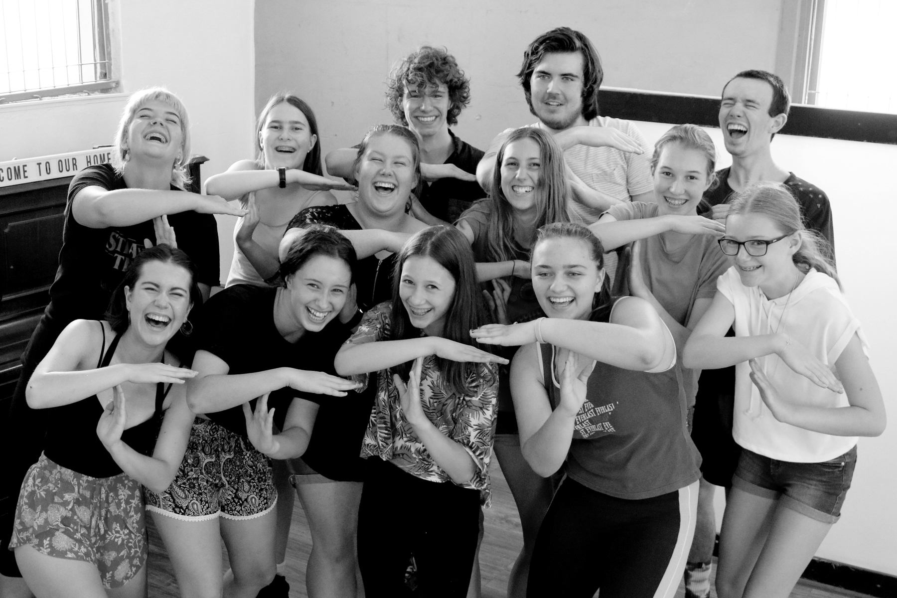 Smiling young people in a drama workshop, making a T shape with their arms.