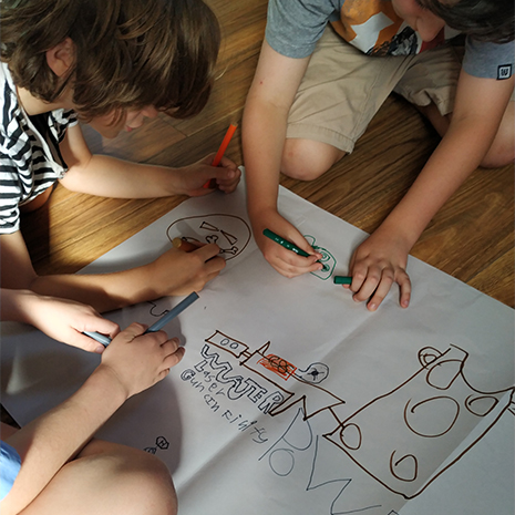 Photo: Kids drawing on paper together in a drama class.